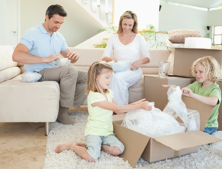 packing boxes: Family unpacking cardboard box together Stock Photo
