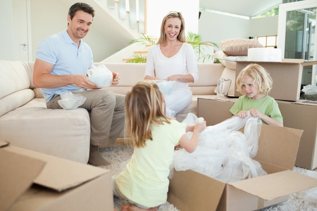 relocation: Family unpacking cardboard box in the living room together