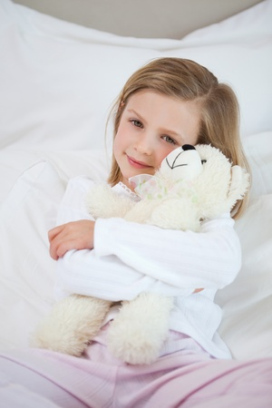 Little girl embracing her teddy on the bed photo