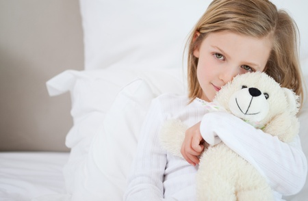 Little girl with her teddy sitting on the bed photo