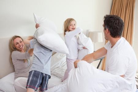 coussins: Ludique famille ayant une bataille d'oreillers ensemble dans la chambre � coucher