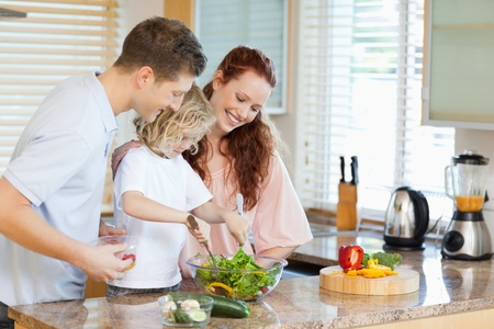 Couple letting their young child stir the salad photo