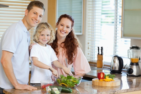 Family preparing salad together photo