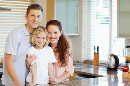 Smiling family standing behind the kitchen counter together photo
