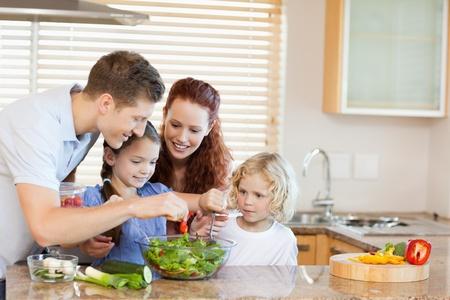 familia comiendo: Joven de la familia la preparación de la ensalada, junto