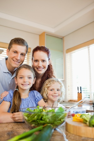 Young family standing together behind the kitchen counter photo