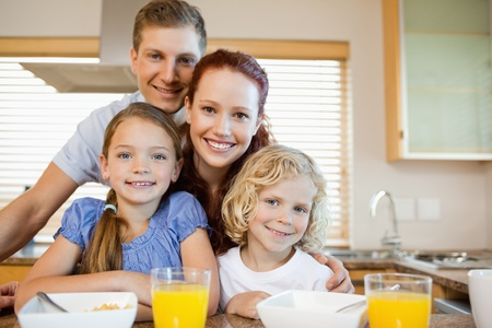 Family together with breakfast behind the kitchen counter photo