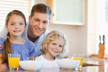 Father together with his children in the kitchen photo