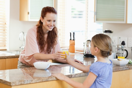 Mother giving her daughter a glass of orange juice photo
