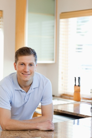 Smiling man leaning against the kitchen counter photo