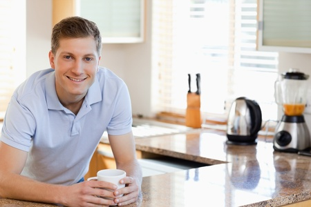 Smiling male leaning against the kitchen counter photo