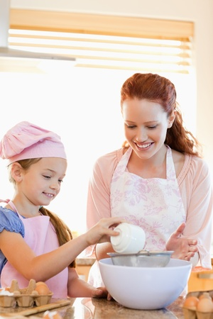 Cheerful mother and daughter preparing dough together photo
