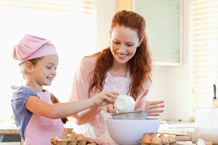 Smiling mother and daughter preparing dough together photo