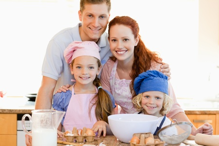 Family together with baking ingredients in the kitchen photo