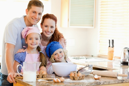 kitchen apron: Family together with baking ingredients behind the kitchen counter Stock Photo