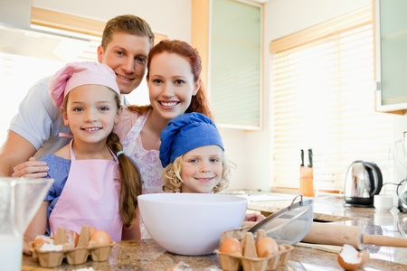 Cheerful happy family preparing dough photo