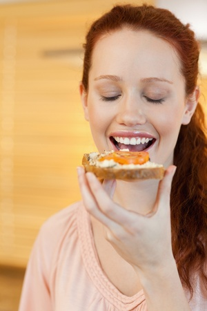 Woman eating a slice of bread with tomato photo