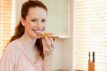 Smiling woman with slice of bread in her hand photo