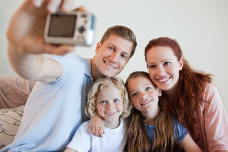 Father taking a family picture on the sofa photo