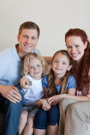 Happy smiling family watching television together photo