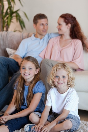 Young family spending time in front of the tv photo