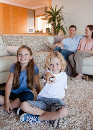 Family watching television in the living room together photo