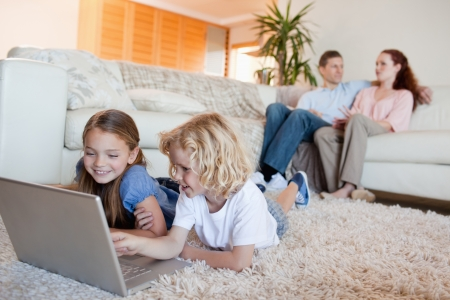 man couch: Siblings using laptop in the living room together