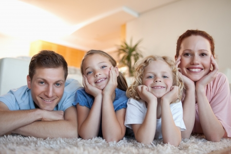 Cheerful smiling family on the carpet photo