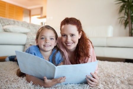 Mother and daughter looking at periodical together photo
