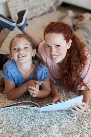 Mother and daughter on the floor reading together photo