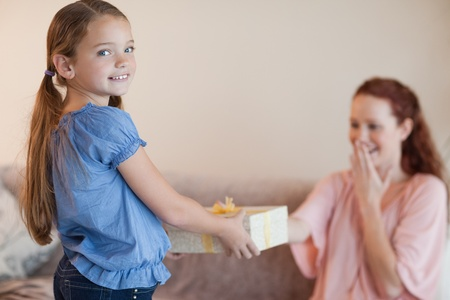 Girl giving her surprised mother a present photo