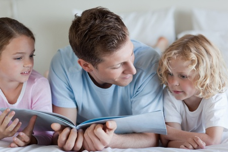 Father reading together with his children photo