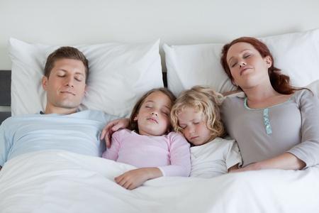 Junge Familie schlafend im Bett zusammen