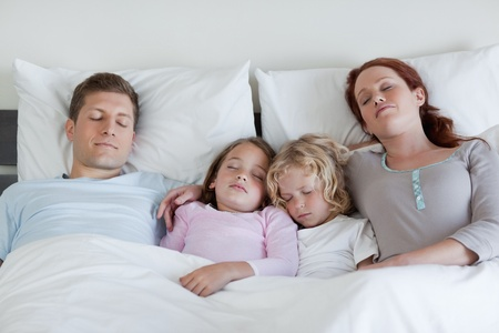 Young family sleeping in the bed together photo