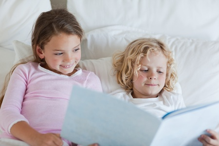 Brother and sister reading bed time story together photo