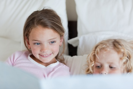 Girl reading a fairy tale for her little brother Stock Photo - 11684113