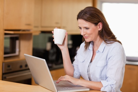 Woman drinking tea while on her laptop photo