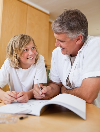 Male helping his son with homework photo