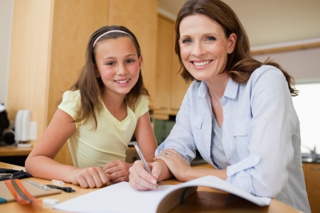 Mother and daughter doing homework together photo
