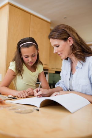 Woman helping her daughter with homework photo