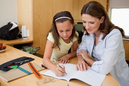 Girl doing homework together with her mother photo