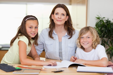 Woman helping her children with their homework photo