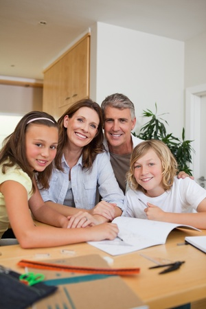 Smiling family doing homework together photo