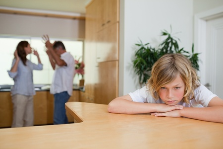 Boy is sad about fighting parents behind him photo