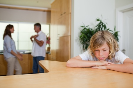 dysfunctional: Sad boy has to listen to his fighting parents Stock Photo