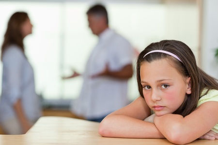 people arguing: Sad girl with her fighting parents behind her Stock Photo