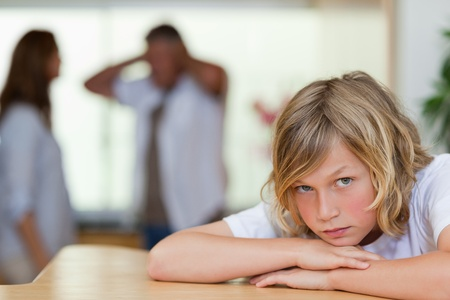 conflict: Sad looking boy with his arguing parents behind him Stock Photo