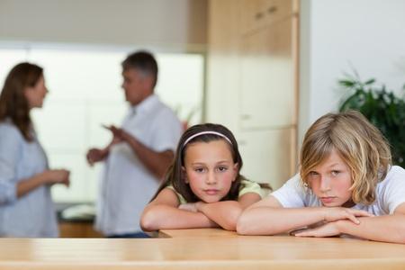 divorcio: Triste hermanos que buscan con sus padres que luchan detr�s de ellos Foto de archivo