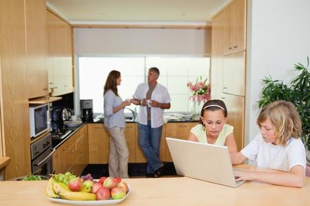 Kinder mit ihrem Laptop in der K�che und Eltern hinter ihnen