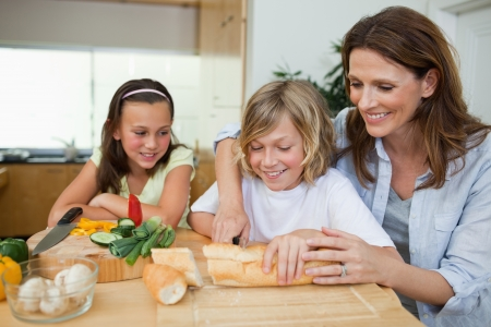 bread slice: Woman making sandwiches together with her children Stock Photo